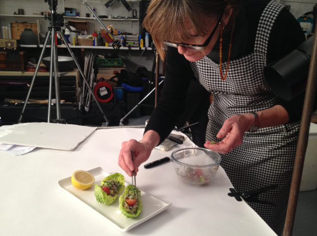 Food stylist making tiny adjustments